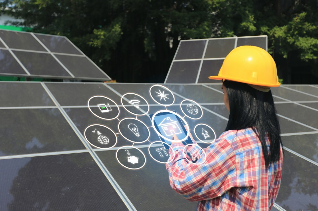 young woman engineer checking solar panel with hologram at solar power plant